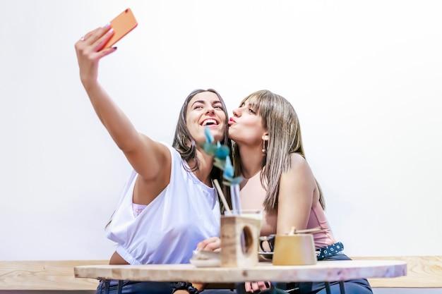 도시의 카페테리아에 앉아 스마트폰으로 사진을 찍는 행복한 십대들