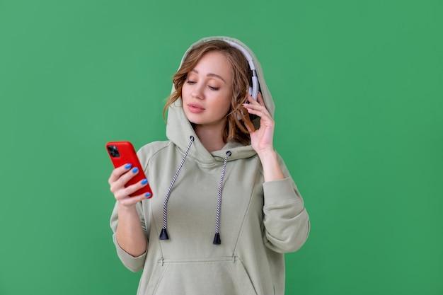 Счастливые зубы улыбка женщина слушать музыку наушники, держа смартфон в руке, глядя на экран кавказская женщина наслаждается подкастом или аудиокнигами, одетая негабаритная толстовка с капюшоном на зеленом фоне крупным планом портрет