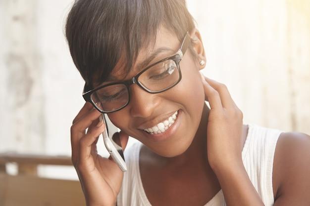 幸せな電話での会話のコンセプト。電話で話していると笑顔の若い女性