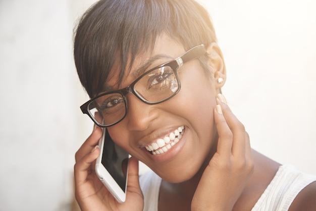 Felice concetto di conversazione telefonica. giovane signora che parla sul telefono e sul sorridere