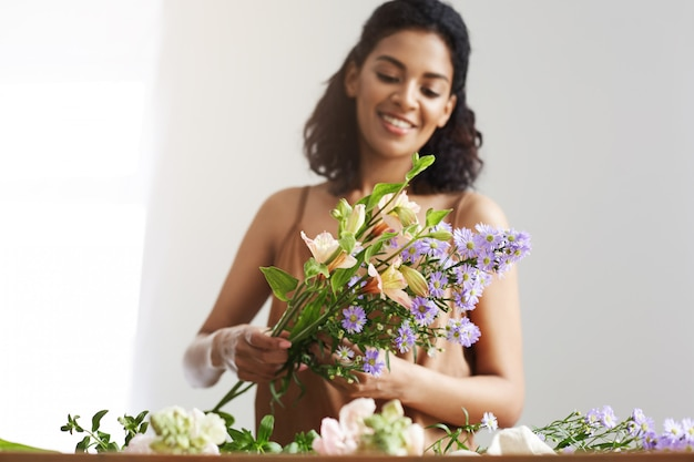 白い壁に職場で花の花束を作って笑って幸せな優しいアフリカ女性。