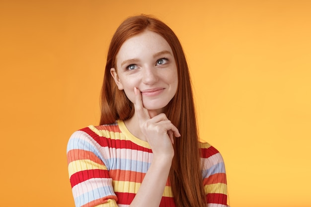 Happy tender feminine redhead 20s girl university student smiling delighted dreaming tasty slice pizza touching lip thoughtful, thinking daydreaming look upper left corner imaging desires.