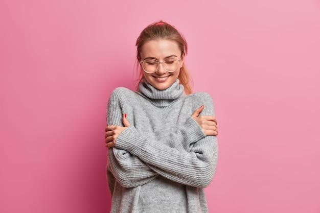 Felice tenera ragazza vestita di grigio caldo maglione oversize, si abbraccia, gode di comfort durante la piovosa giornata autunnale, indossa occhiali trasparenti sorride piacevolmente