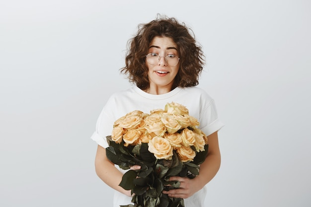 Happy tender girlfriend receive bouquet of beautiful flowers, holding roses and sighing surprised