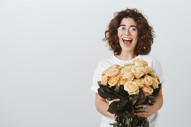 幸せな優しいガールフレンドは美しい花の花束を受け取り、バラを持って驚いてため息をつく
