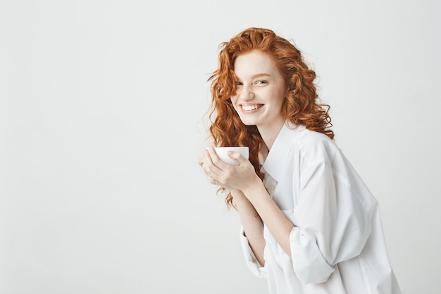 Happy tender redhead girl in shirt smiling holding cup sitting on table