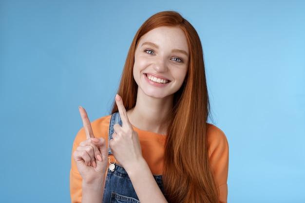 Счастливая нежная рыжая девушка искренне улыбается с белыми зубами полезно смотреть в камеру взволнованно дайте руку, указывающую в левый верхний угол, представить предложение о продаже рекомендую попробовать промо стоя на синем фоне