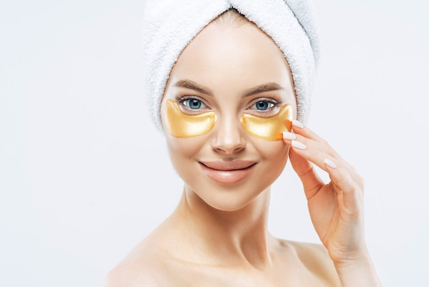 Happy tender woman applies golden patches under eyes