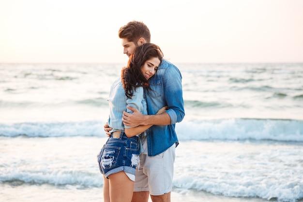 Счастливая нежная молодая пара стоя и обниматься на пляже