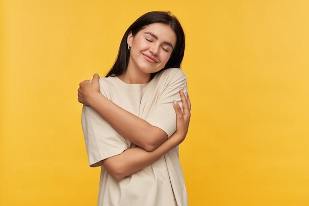 黒い髪と目を閉じた白い t シャツを着た幸せな優しい若い女性が立って、黄色の壁に手で抱きしめている