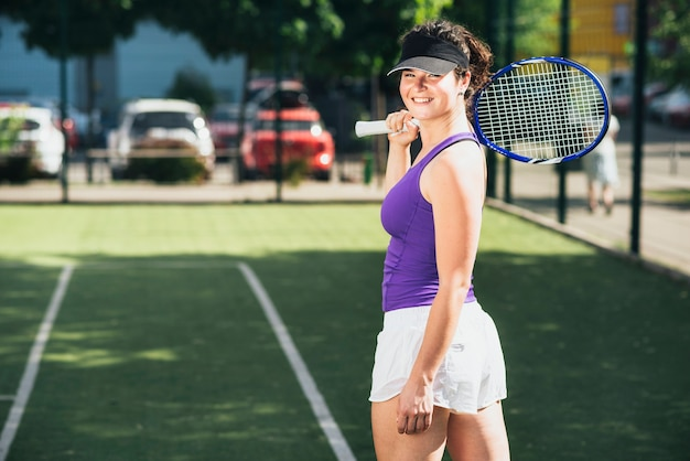 Happy tennis player with racket in hand