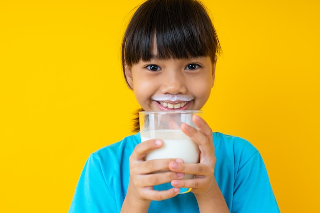 Happy thai kid holding glass of milk isolated, young asian girl drinking milk for strong health on yellow