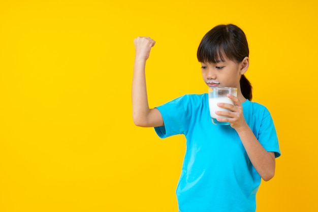 Happy thai kid holding glass of milk isolated, young asian girl drinking milk for strong health