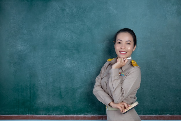 Счастливый тайский учитель в официальной одежде позирует перед доской