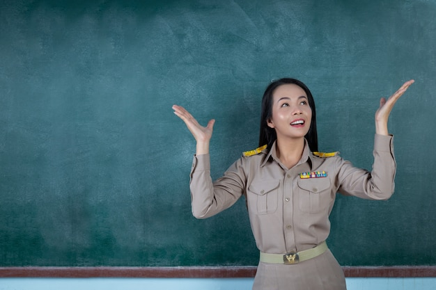 Happy thai teacher in official outfit  acting in front of  backboard