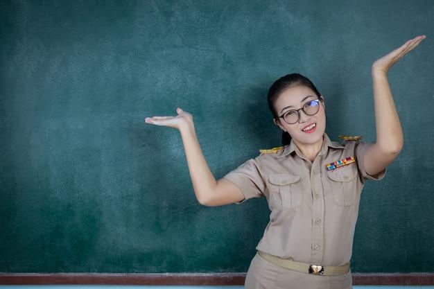 Insegnante tailandese felice in attrezzatura ufficiale che posa davanti alla lavagna