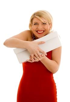 Счастливая благодарная девушка в красном платье держит белую коробку