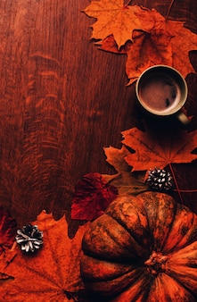 Happy thanksgiving autumn background with pumpkin, cones, cup of coffee and leaves