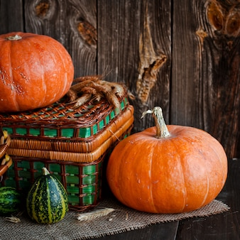 Happy thanksgiving background, pumpkins wicker basket on old wooden table.