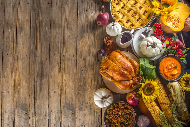 幸せな感謝祭のコンセプト。サヤインゲン、マッシュポテト、クランベリーソース、カボチャスープ、秋の果物、野菜など、伝統的な食事と食べ物を使った感謝祭のお祝いディナーの設定