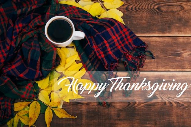 Концепция счастливого благодарения с оранжевыми тыквами, желтыми листьями и чашкой кофе на деревянном
