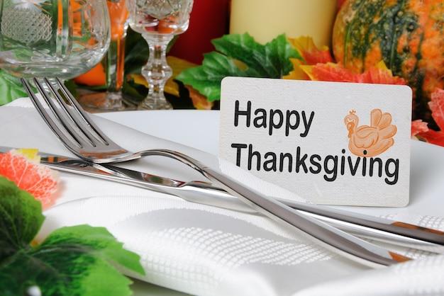테이블에 냅킨과 칼 붙이와 함께 접시에 행복 한 추수 감사절 카드
