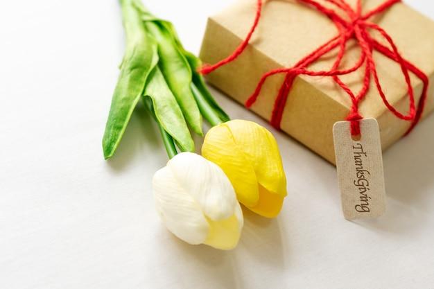 ハッピー感謝の日。ギフトボックスと花と紙のタグ