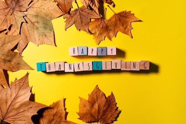 С днем благодарения с кленовыми листьями и деревянным кубиком