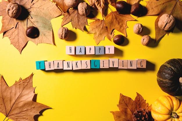 С днем благодарения с кленовыми листьями, орехом, тыквой и деревянным кубиком