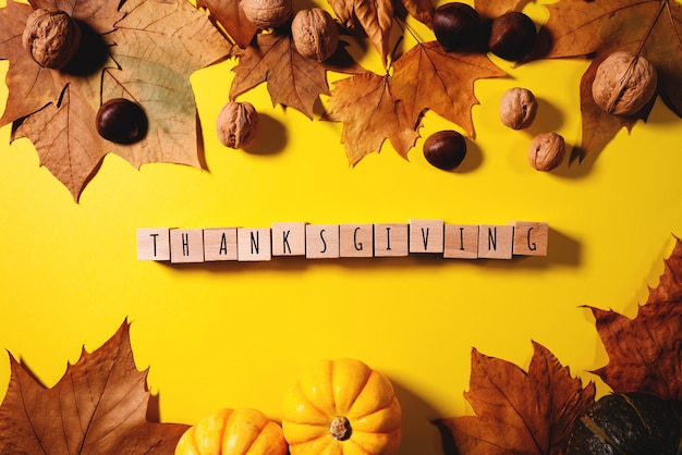 Happy thanksgiving day with maple leaves, nut, pumpkin and wooden cube
