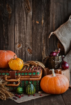 Happy thanksgiving , pumpkins and wicker basket on old wooden table.