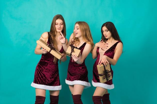 異なる髪の色、ギフトバッグ付きのクリスマスの衣装を着た雪の乙女の幸せな3人の美しい女の子。