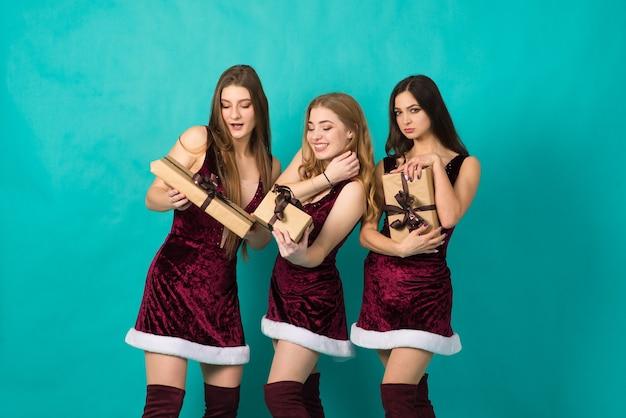 異なる髪の色、クリスマスの衣装を着た雪の乙女、ギフトバッグを持つ幸せな3人の美しい女の子。
