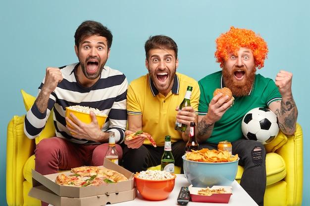 Счастливые трое друзей - футбольные фанаты, смотрят футбол, позируют на диване в гостиной, едят фаст-фуд, пьют холодное пиво