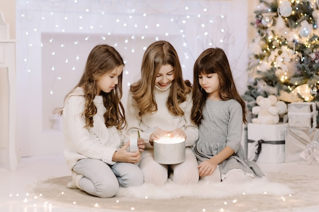 벽난로로 마법의 크리스마스 선물을 여는 행복한 세 명의 작은 자매