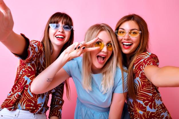 幸せな3人の笑顔のスタイリッシュな女の子が楽しんで、平和のジェスチャーと笑顔、流行のヒップスターサングラスとファッションカラーマッチングの服、友情の目標、ピンクの壁を示しています