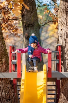 Happy three-year baby girl in jacket on slide