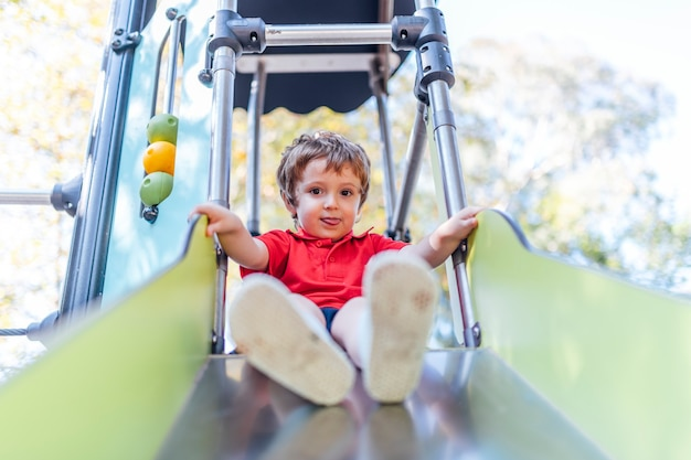 Happy three year old boy looking straight ahead playing on a slide in a playground