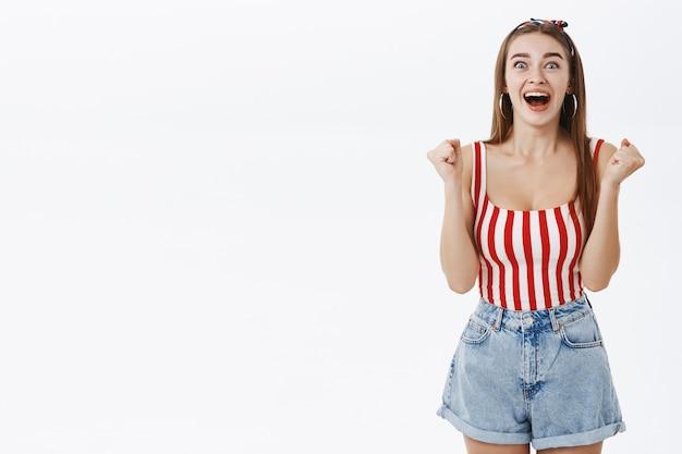 Счастливая взволнованная взволнованная женщина в стильной одежде в стиле пин-ап поднимает сжатые кулаки от радости и радуется и кричит от счастья