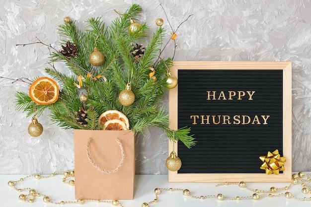 Счастливый четверг текст на черной доске для писем и праздничный букет еловых веток с рождественским декором в ремесленном пакете на столе.
