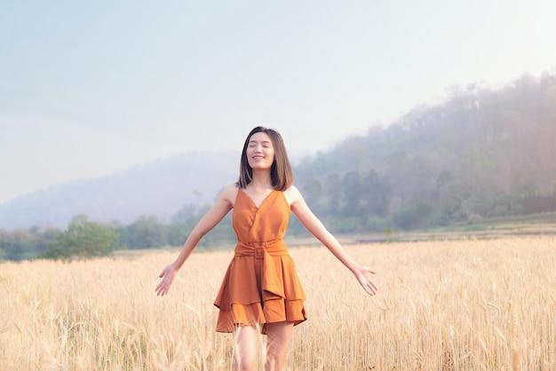 Happy time asian woman in barley field