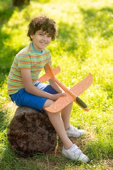 Happy time. friendly cute smiling boy with dark curly hair with toy plane sitting on tree stump in park on fine day