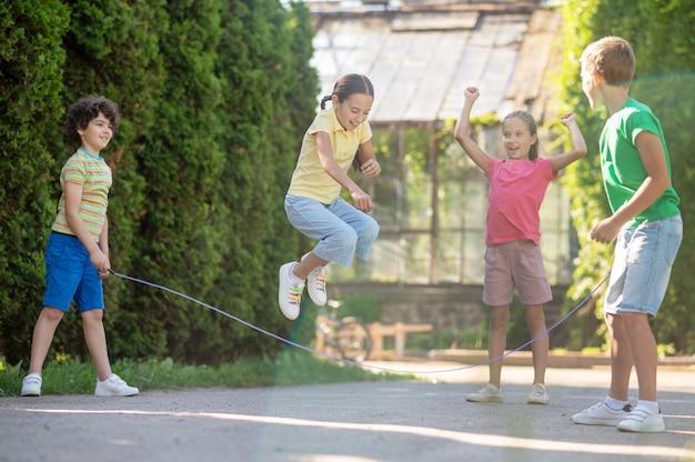 행복한 시간. 화창한 날에 녹색 공원에서 친구들과 줄넘기를 하는 땋은 머리를 가진 즐거운 감정적 소녀
