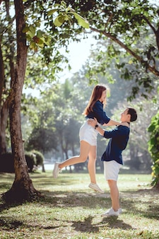 Happy time of a lovely asian couple in the park on day time, man hold up his girlfriend.