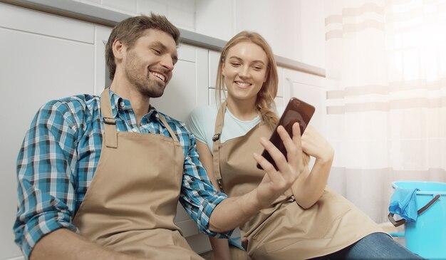 幸せな疲れたカップルは、キッチンクリーニングとスマートフォンで床に座った後の休息があります。