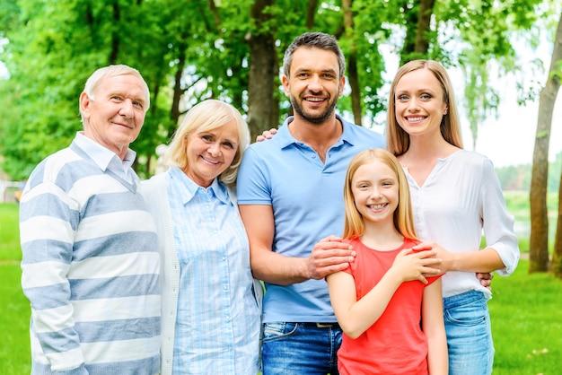 家族になって幸せです。 5人の幸せな家族がお互いに結合し、一緒に屋外に立っている間笑顔