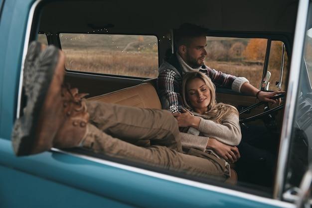Счастлив быть рядом. привлекательная молодая женщина отдыхает и улыбается, пока ее парень за рулем мини-фургона в стиле ретро