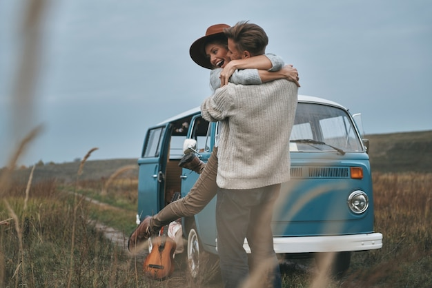 주변에 있으면 행복합니다. 파란색 복고풍 스타일의 미니 밴 근처에 서있는 동안 포용하고 웃는 아름다운 젊은 부부