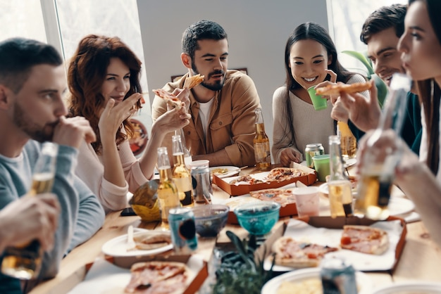周りにいて幸せです。屋内でディナーパーティーをしながらピザを食べて笑顔でカジュアルな服装の若者のグループ
