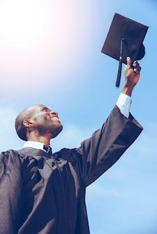 졸업해서 행복합니다. 푸른 하늘을 배경으로 박격포 보드를 들고 졸업 가운을 입은 행복한 젊은 아프리카 남자의 낮은 각도 보기